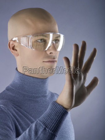 man wearing goggles with hand up