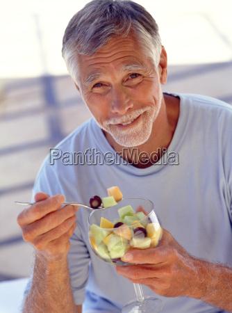 portraet af moden mand spise frugt