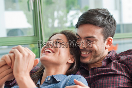 romantisk unge par griner pa sofaen