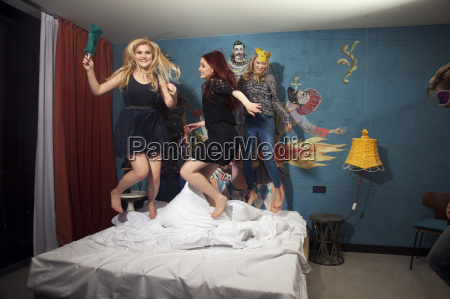 four adult friends dancing on hotel