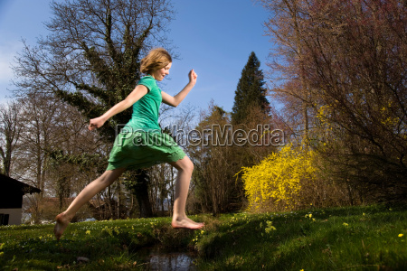 girl jumping over creek