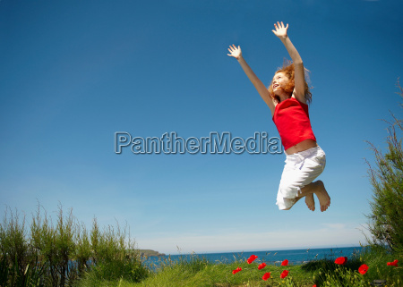young girl jumping with arms up