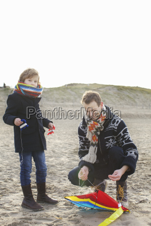 mid adult man preparing kite for