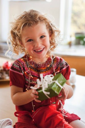 young girl opening present smiling