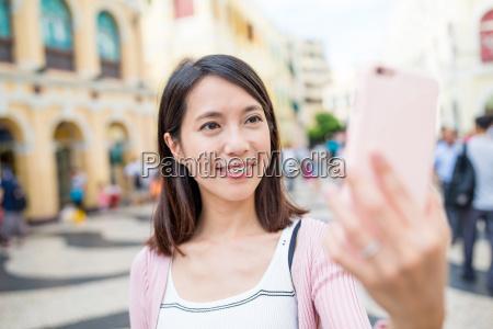 kvinde bruger mobiltelefon til at tage