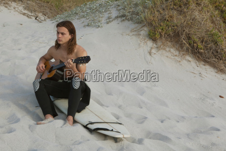 young man playing guitar on beach