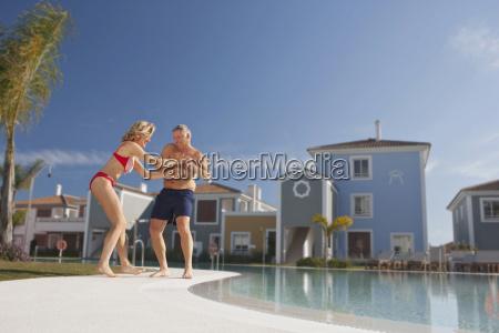 mature man pulling woman into pool