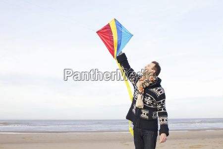 mid adult man holding up kite