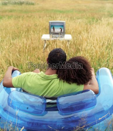 couple sitting outside watching tv