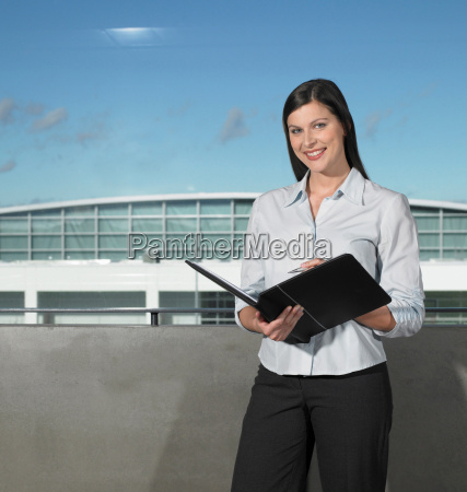 businesswoman smiling holding book
