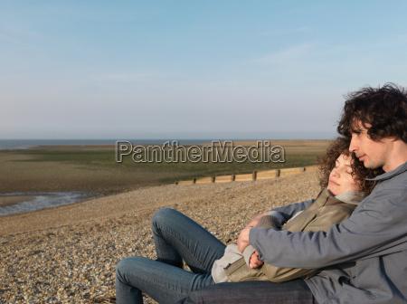 couple cuddling on pebbled beach