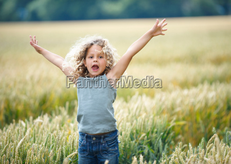 young girl jumping out of cornfield