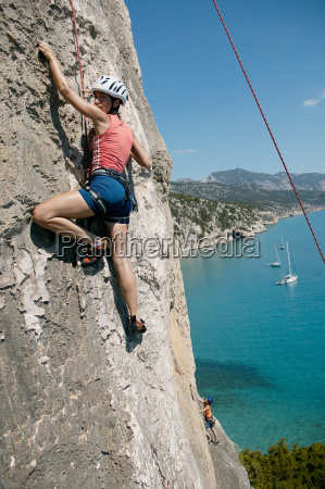 woman rock climbing bay in background