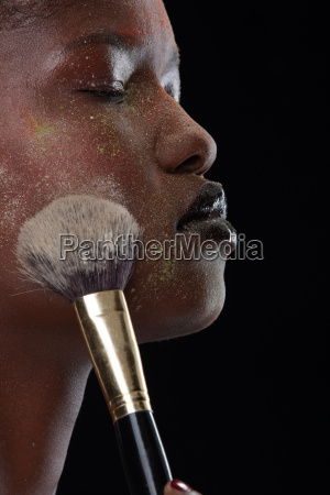 woman brushing makeup on her face