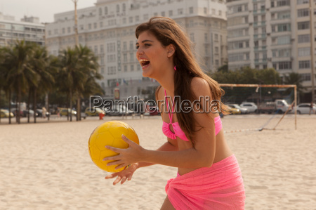 young woman holding yellow beach ball