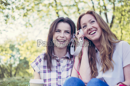 two young female friends drinking coffee