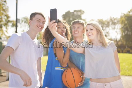 four young adult basketball players taking
