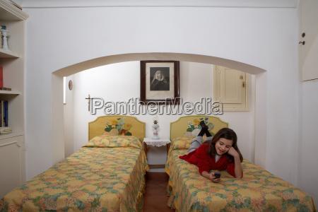 girl lying on bed using phone
