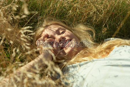 young woman lying in long grass