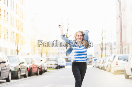 excited young woman dancing along street