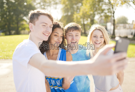 four young adult basketball players posing