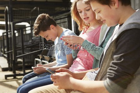 four boys and girls reading smartphone