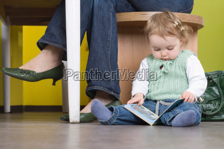 young girl on floor with book