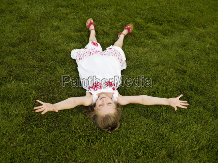 girl lying arms outstretched on a