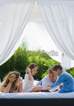 family having breakfast on bed in