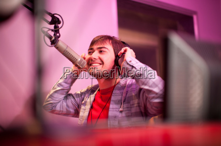 young man broadcasting in recording studio