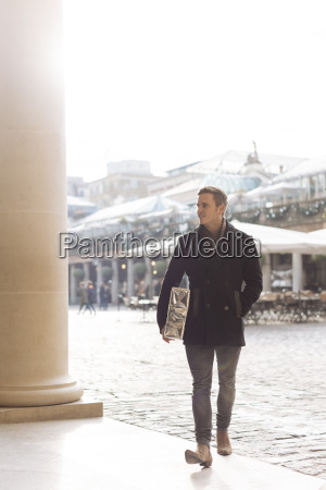 young man carrying gift in covent
