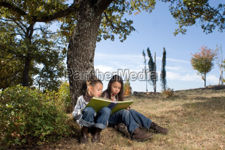 two young girls reading a book