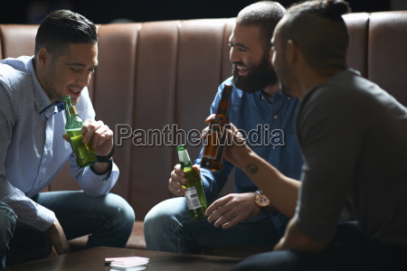 three male friends chatting and drinking