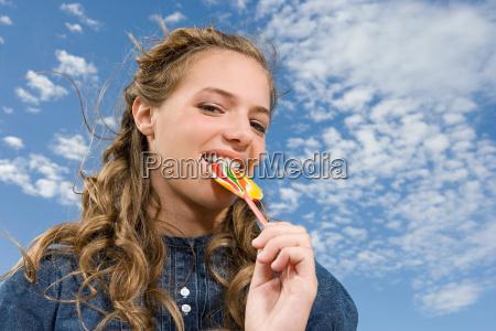 teenage girl eating a lollipop