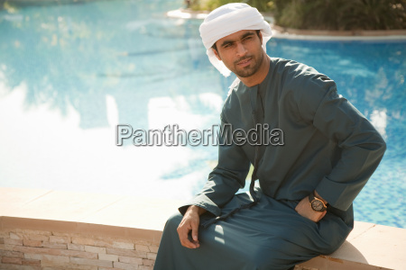 middle eastern man sitting by swimming