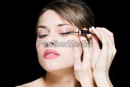 kvinde anvender eyeliner