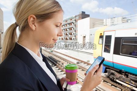 forretningskvinde med kaffe og smart telefon
