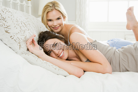 young women lying on bed