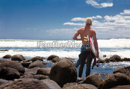 young adult male surfer watching sea