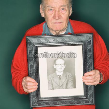 senior man holding a portrait of