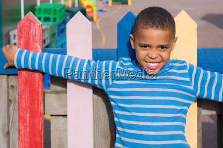 boy leaning on fence