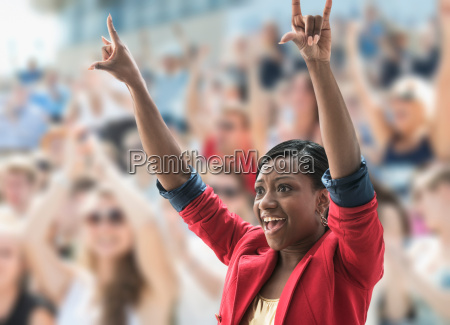 excited woman in crowd making hand