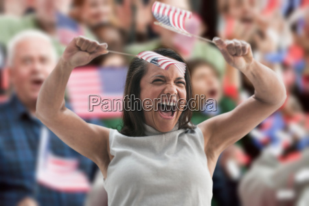 excited woman waving american flags at