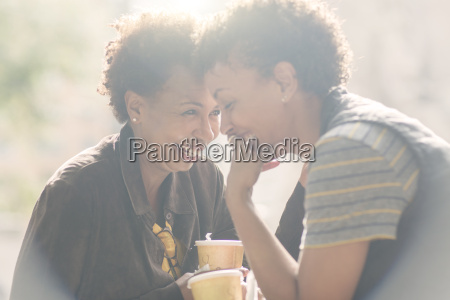 two mature female friends laughing whilst