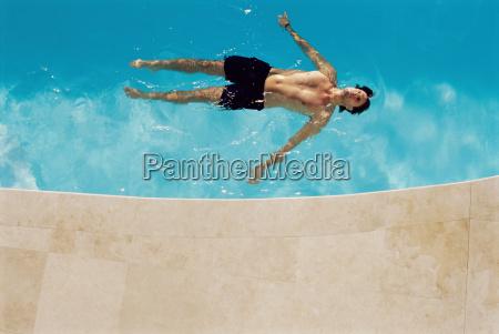 man floating in swimming pool