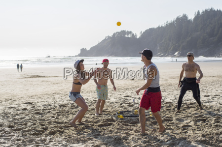 four adult friends playing with ball