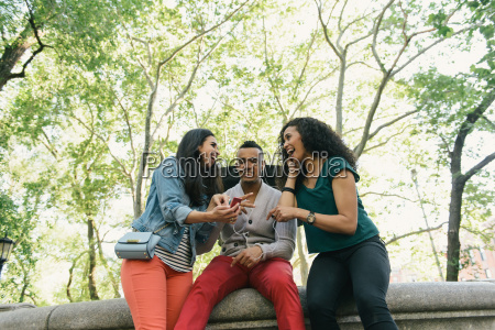 three mid adult friends reading smartphone