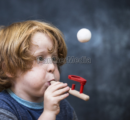 young boy playing game blowing ping