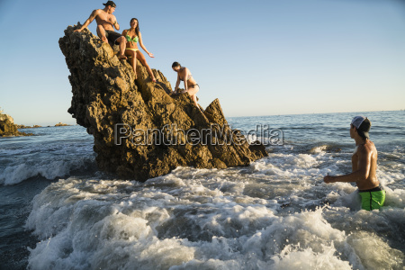 adult friends wading and climbing on