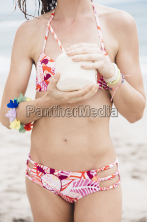 mid adult woman on beach drinking